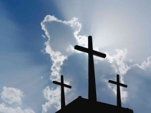 Three crosses in silhouette against a blue sky.