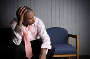 A person sitting in a waiting room has their hand on their head and their tie loosened in frustration and exhaustion
