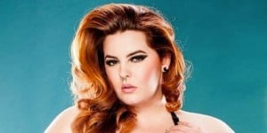Plus-size model Tess Munster looks seductively at the camera against a teal background