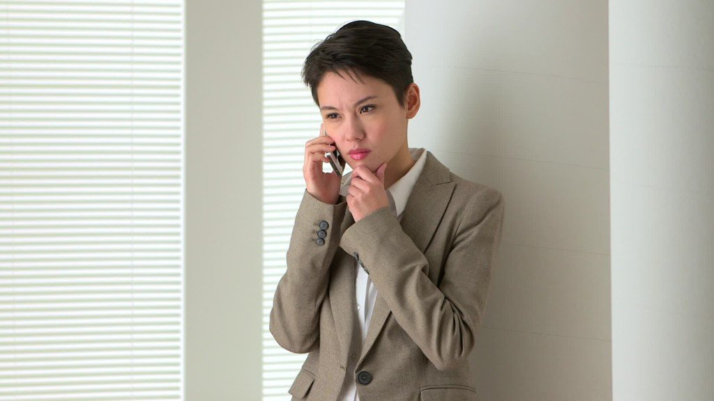 Young person dressed masculinely, talking on a cell phone, looking serious