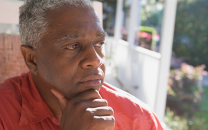 Older man looking thoughtfully, contemplatively into the distance from his porch
