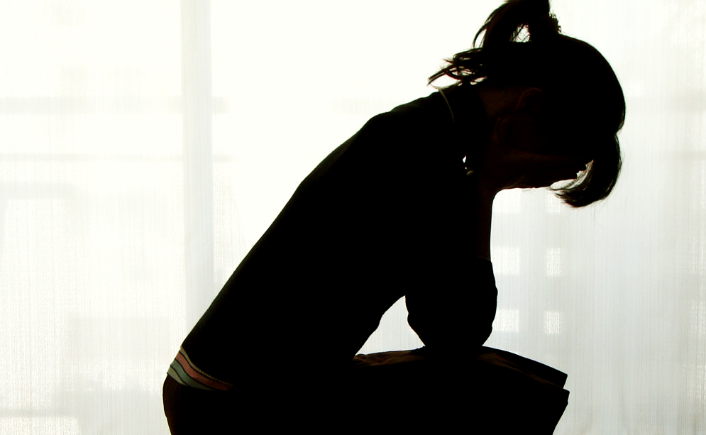 Silhouette of a person with their head in their hands, looking distraught