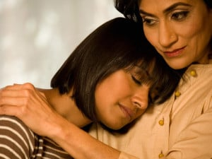 Older person hugging a younger person who looks relieved to be supported