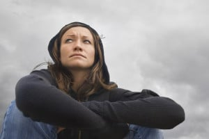 A feminine-presenting person hugging her knees with a pensive expression.