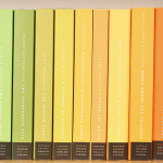 Books lined up on a shelf in order by color, creating a rainbow