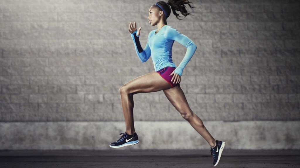Fit person running, with a gray wall in the background