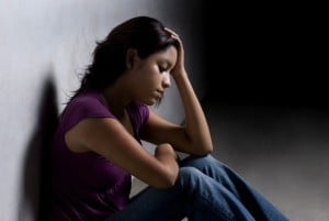 Young person sitting against a wall with their head in their hands, visibly upset