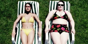An elevated view of a thin person and a fat person lying side by side on lounge chairs