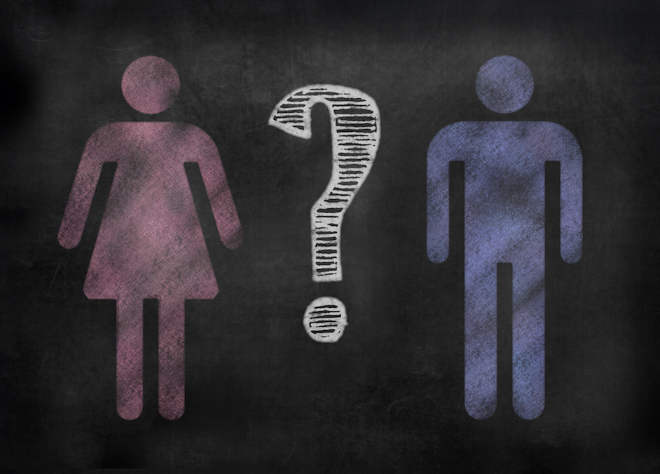 """Pink """"woman"""" symbol and blue """"man"""" symbol drawn on a chalkboard with a question mark in the middle"""