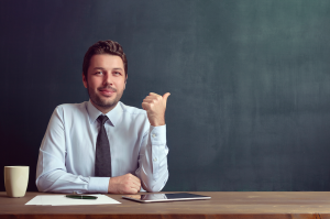 Teacher sitting at a desk in front of a chalkboard