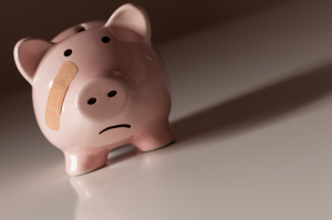 A piggy bank with a sad face and a bandaid on its face