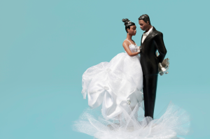 Wedding cake toppers against a teal background