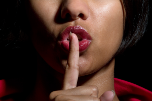 "A close-up of a person with their finger up to their lips, saying ""Shhh"""