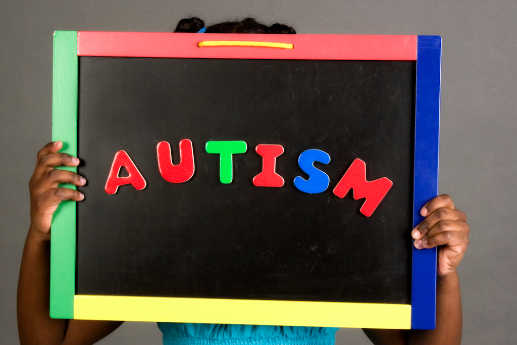 "A young child holds up a chalkboard that reads ""AUTISM"" in colorful letters"
