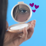 Person looking in compact mirror