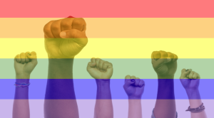 Fists are in the air, overlayed with a rainbow flag