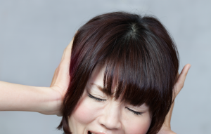 Person blocking their ears, frustrated