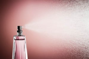Glass bottle of pink perfume spraying a fine mist against a pink background