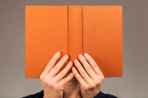 Person holding up an orange book, hiding behind it, deep in reading