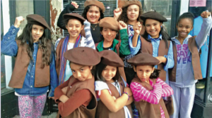 A group of 9 girls wearing brown berets, raising their fists or crossing their arms