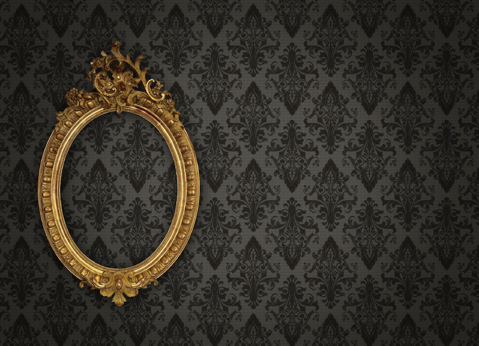 A mirror without glass hangs against a wallpapered wall