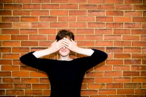 A person standing against a brick wall has their hands over their eyes, covering them