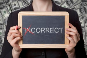 "A person, against a background of money, holds up a chalkboard that says ""Incorrect"" with the ""in"" crossed out"