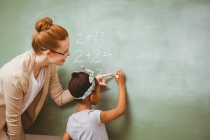 A teacher helping a young child with math at the chalkboard