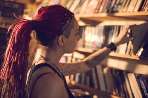 Young student choosing a book from bookshelf in a library