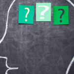 A human head is drawn on a chalkboard. In the brain are three slips of green paper with question marks on them.