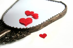 A handheld mirror lays against a table with cut-out red paper hearts strewn about