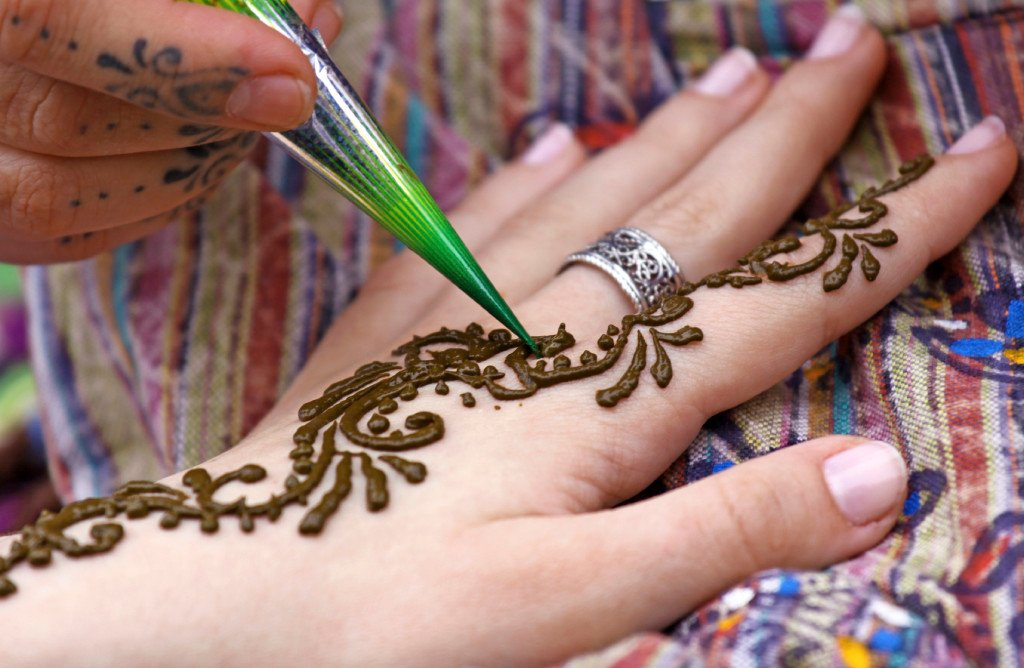 A hand is set against a table, being adorned with henna