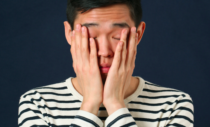 Person in a black-and-white striped shirt against a dark blue background, holding their hands up to their face is disappointment