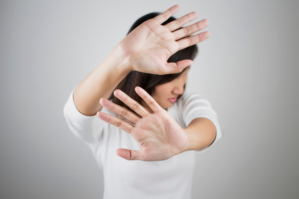 Person holding up their arms, as if asking someone to stop
