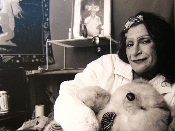 A black-and-white image of Sylvia Rivera, holding onto a teddy bear