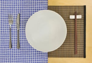 A plate set with a fork, knife, and chopsticks