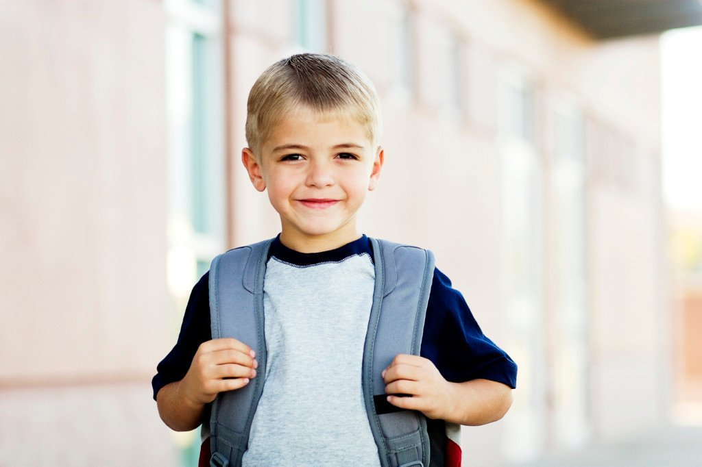 Young child with a backpack, going to school