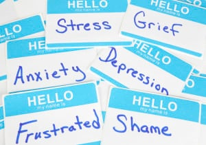 """A pile of name tags, reading """"Stress,"""" """"Grief,"""" """"Depression,"""" """"Anxiety,"""" etc."""