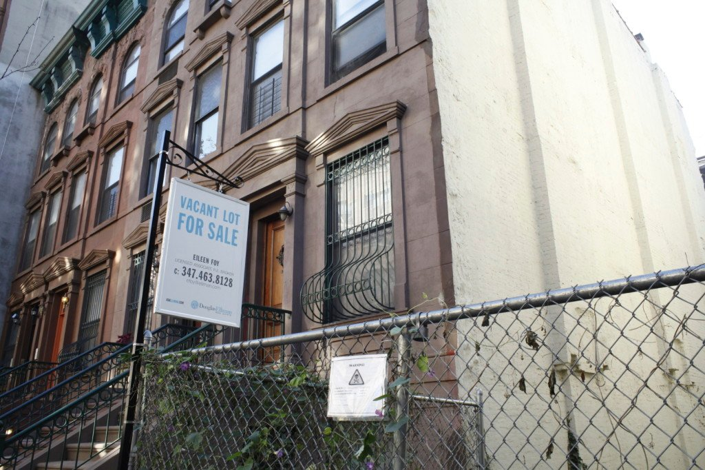 Next to brownstones, a vacant lot is for sale in Harlem