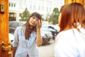 Person looking in a mirror on the street, fixing themselves