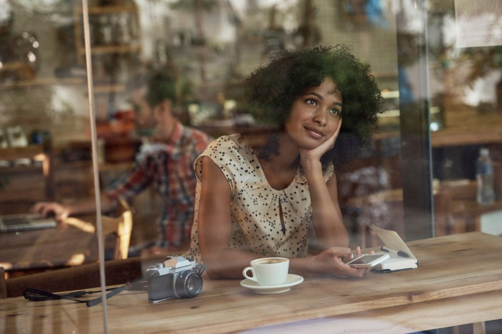 A person in a coffee shop window, daydreaming and pondering