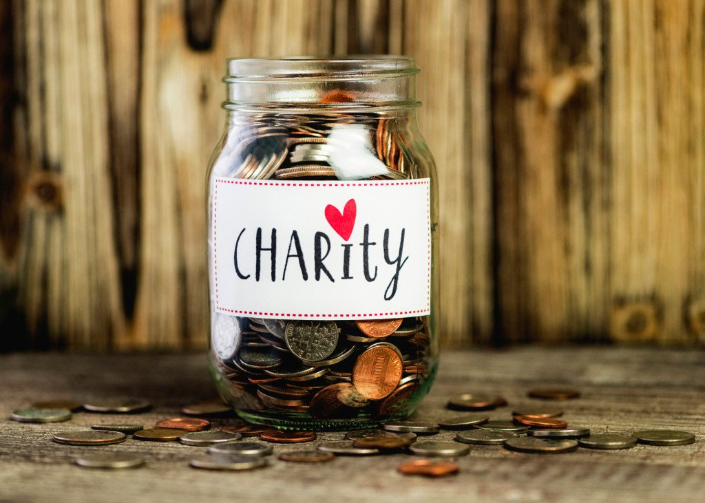 "A jar of coins that reads ""Charity,"" with a heart dotting the I."