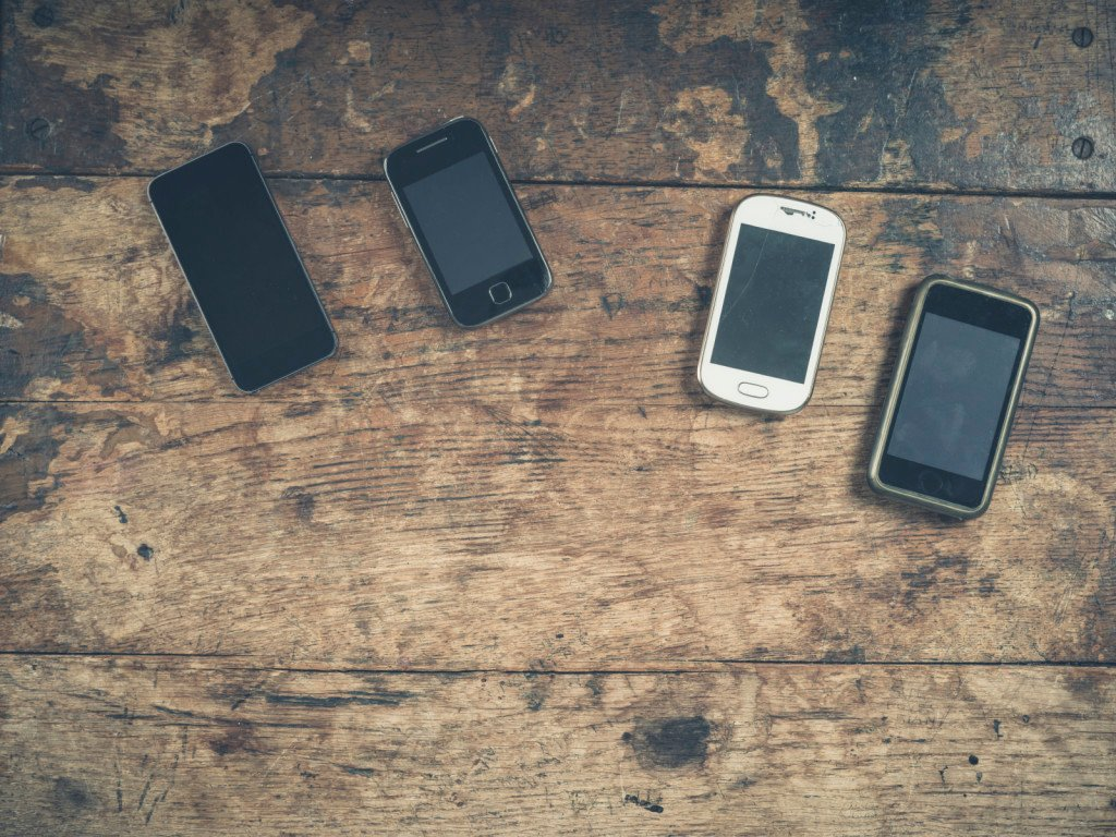 A selection of smart phones on a wooden table