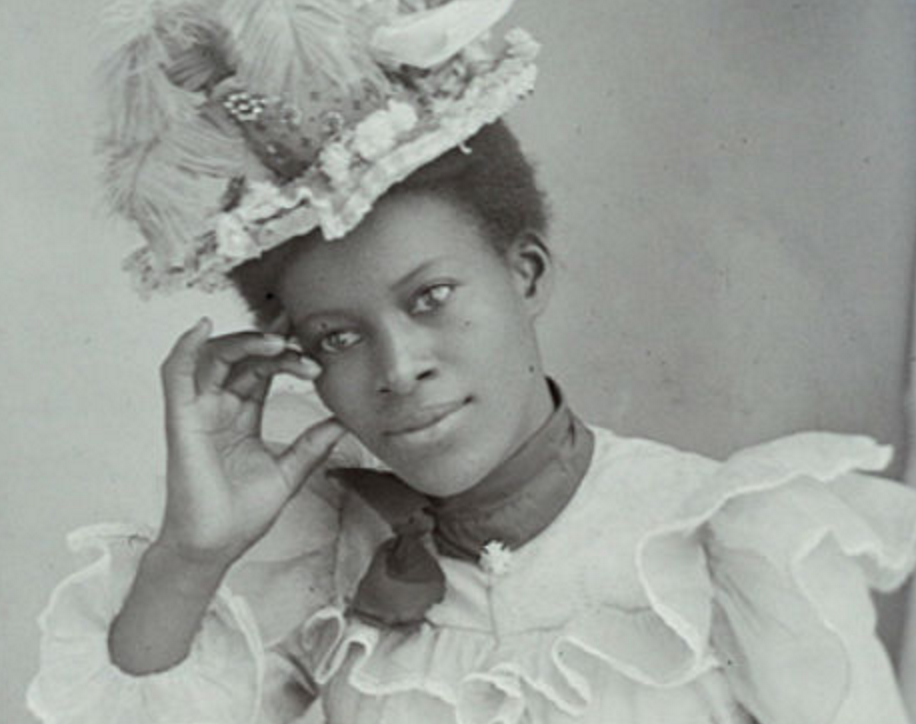 A person in an ornate hat and dress looks pensively into the camera, their hand touching their face.