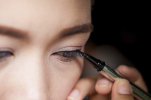 Closeup of a person applying eyeliner.