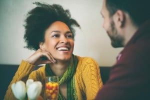 A young couple is talking at a coffee shop. One of them is smiling with their hand against their cheek; the other, out of focus, is seen from behind, smiling back at them.