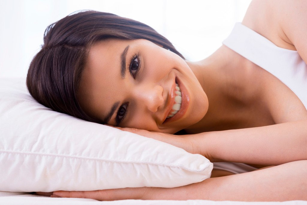 A person rests on their side, their head on a pillow, smiling.