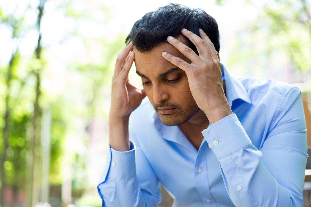 A stressed person has their hands on head, sitting outside.