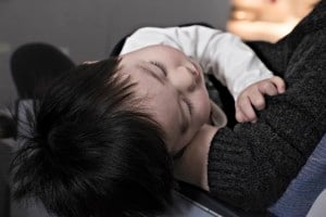 A toddler rests on someones lap.