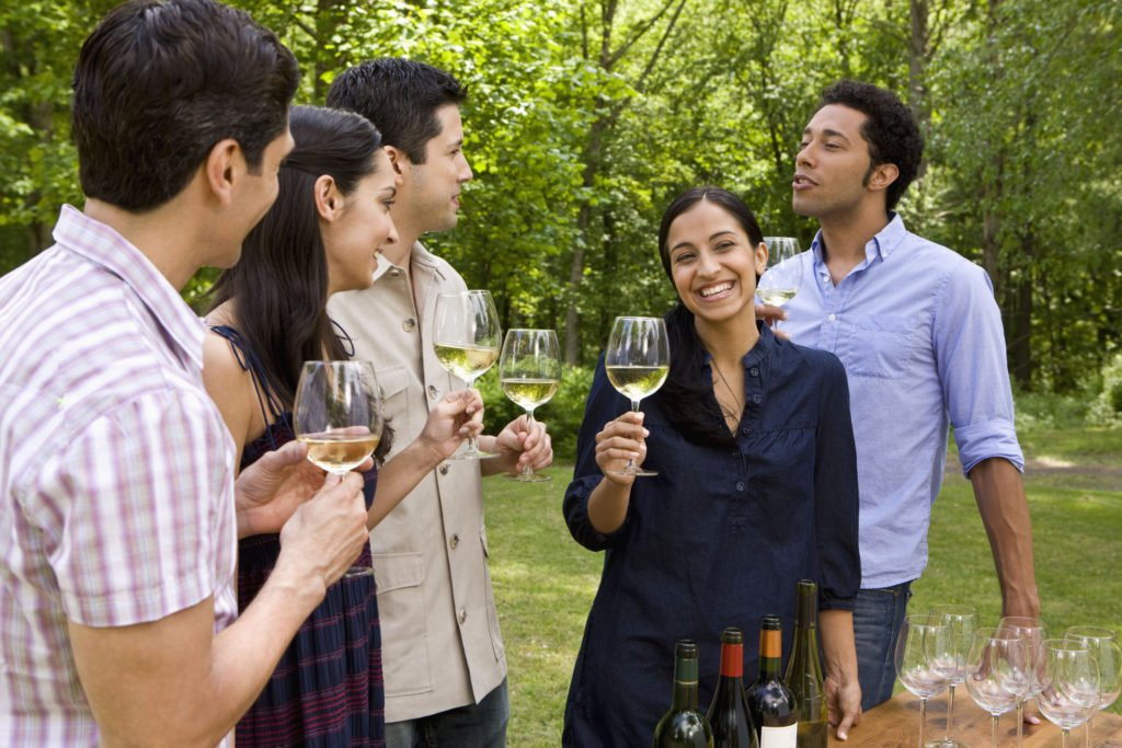 A group of young people drinking white wine together outdoors.